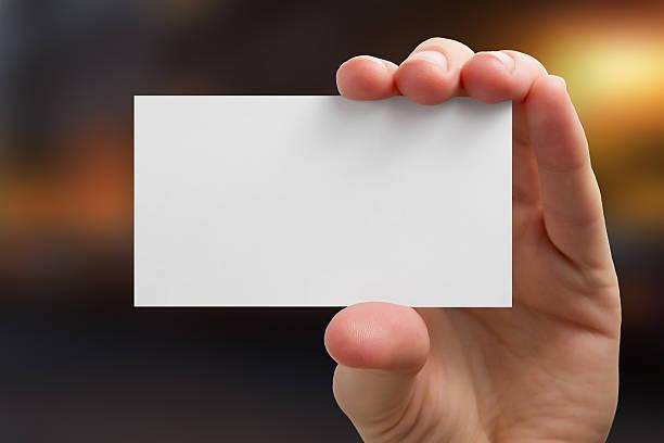 Mão segurando cartão de negócio em branco sobre fundo desfocado - foto de acervo