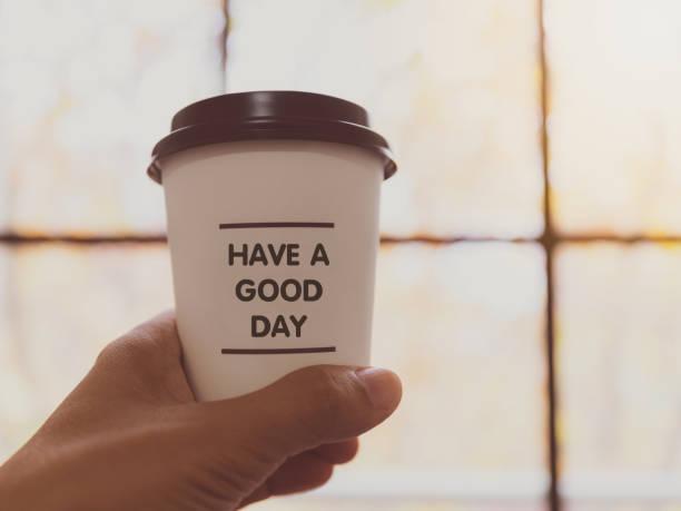 """hand, die weißen kaffee pappbecher mit text """"have a good day"""" auf unscharfen hintergrund. vintage-ton, ermutigung und motivation. - glückliche montagszitate stock-fotos und bilder"""