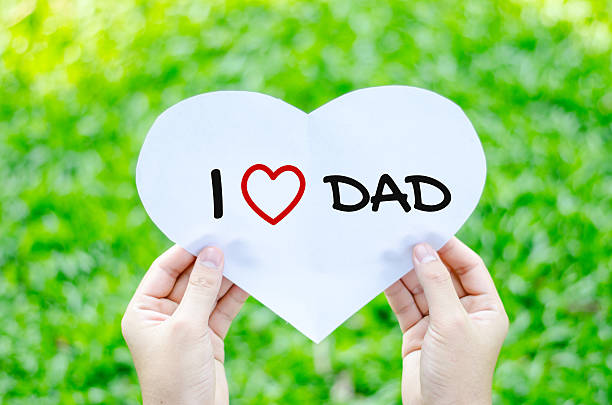 Hand holding white heart paper with I love dad text stock photo