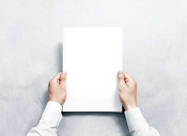 hand holding white journal with blank cover mockup. - covering stock photos and pictures