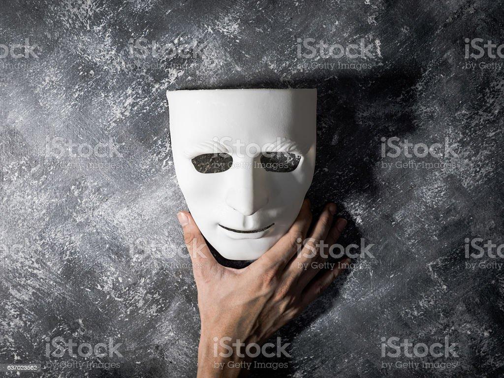 Hand holding white mask on gray grunge background. stock photo