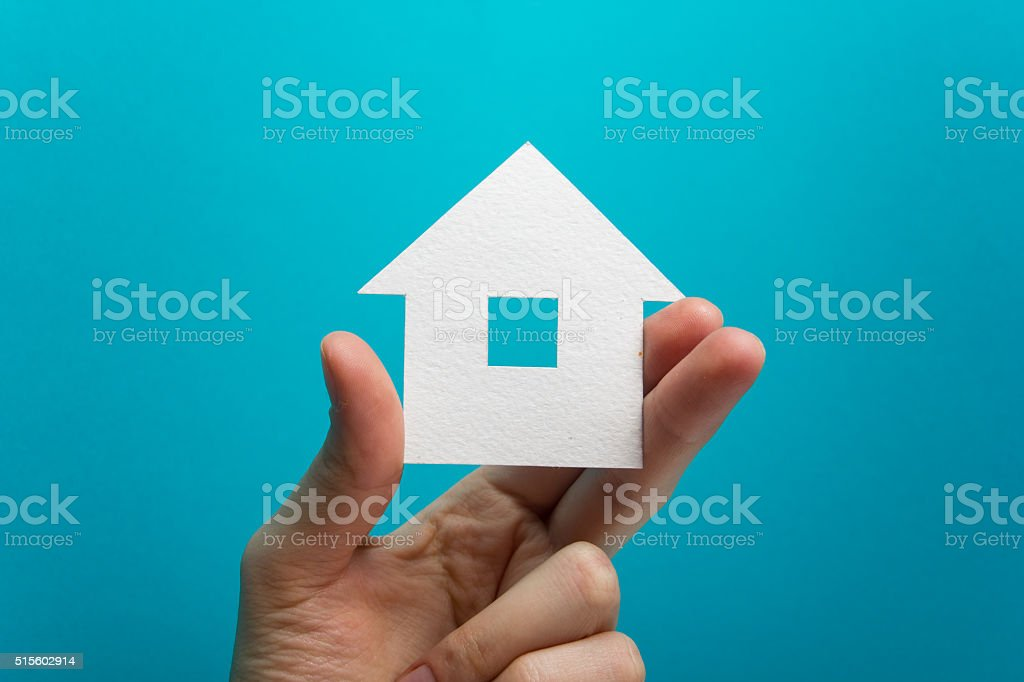 Mano agarrando Libro Blanco Asamblea figura en fondo azul. Real - foto de stock