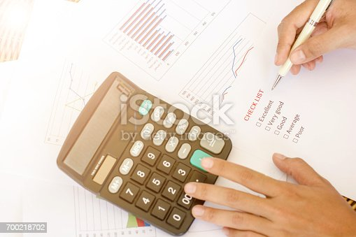 istock Hand holding white pen on check list with calculator on white paper graph on wooden table for choice. 700218702