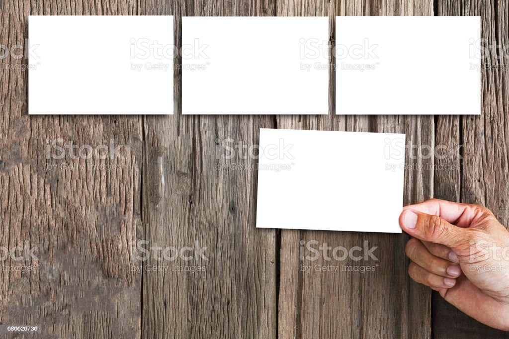 Hand holding white photo frame, some frames on wooden background royalty-free stock photo