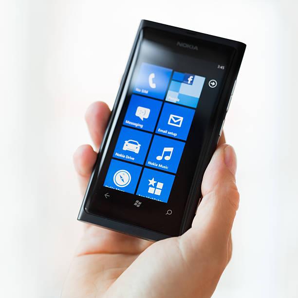 mano che tiene il telefono intelligente windows - windows 7 foto e immagini stock