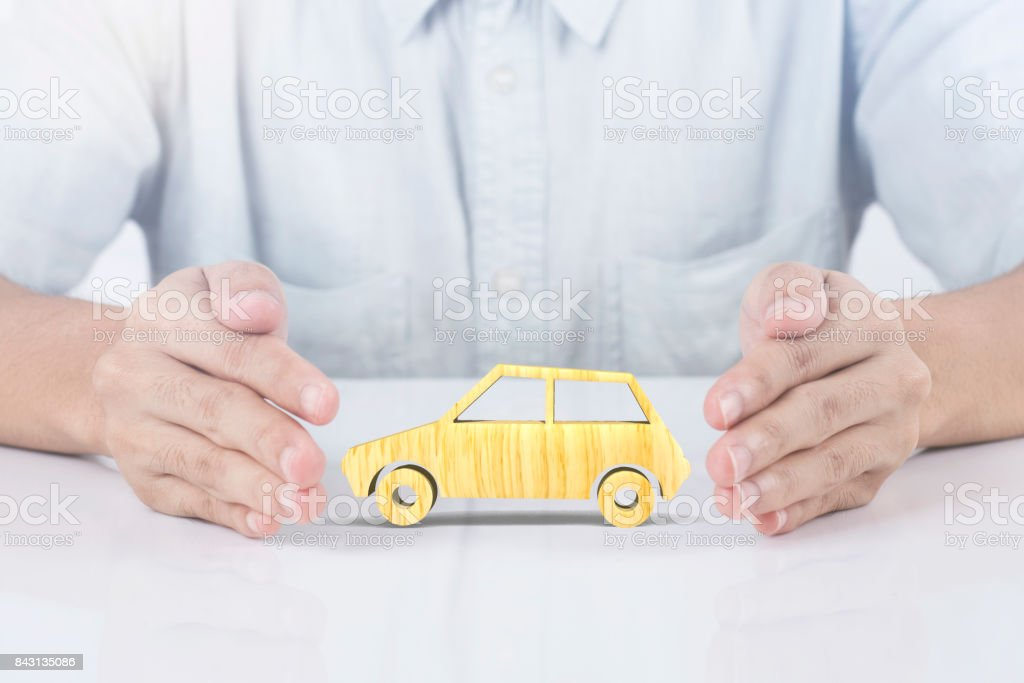 hand holding wood car insurance. concept accident prevention coverage. stock photo