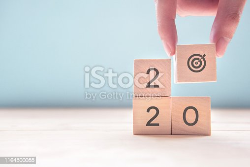 istock Hand holding wood wooden cubes with New year 2020 and goal icon concept. 1164500055