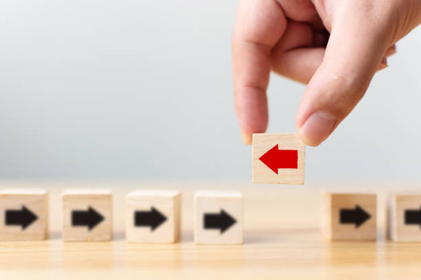 Hand holding wooden block with red arrow facing the opposite direction black arrows, Unique, think different, individual and standing out from the crowd concept Hand holding wooden block with red arrow facing the opposite direction black arrows, Unique, think different, individual and standing out from the crowd concept inconvenience stock pictures, royalty-free photos & images