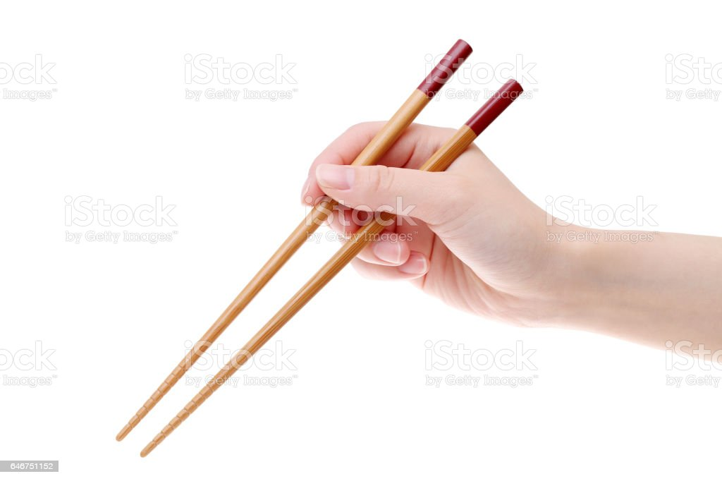 Hand holding wooden chopsticks stock photo