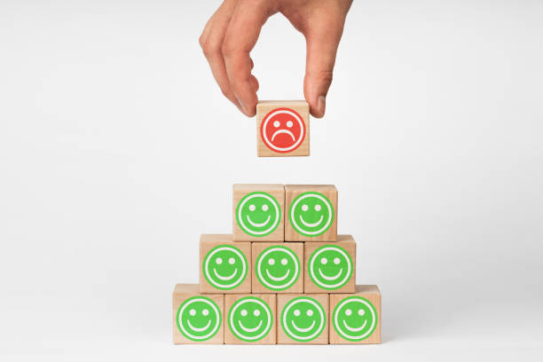 Hand holding wooden cube with face emotion. Concept of customer service experience and business satisfaction survey. stock photo