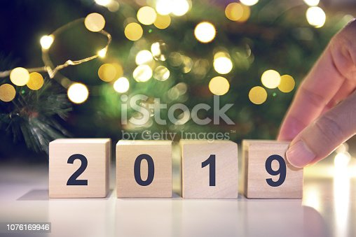 1009979852 istock photo Hand holding Wooden cubes with Happy new year 2019 with light bokeh background. 1076169946