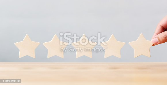 1133580311 istock photo Hand holding wooden five star shape on table. The best excellent business services rating customer experience concept 1138059133