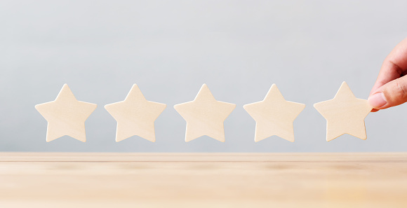 917079212 istock photo Hand holding wooden five star shape on table. The best excellent business services rating customer experience concept 1138059133