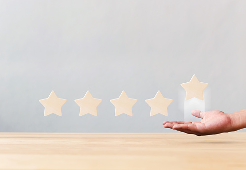 917079212 istock photo Hand holding wooden five star shape on table. The best excellent business services rating customer experience concept 1159323787