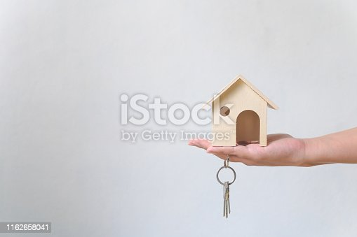 Hand holding wooden house and home keychain. Property investment and house mortgage financial real estate concept