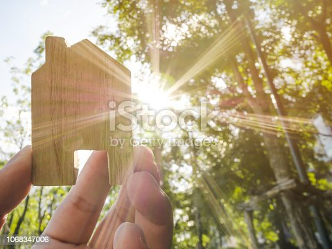 958039576istockphoto Hand holding wooden house with green forest background blurred and sun lighting 1068347006