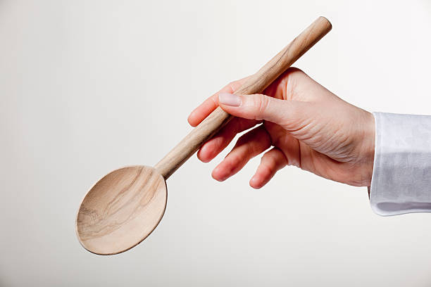 Hand holding wooden spoon stock photo