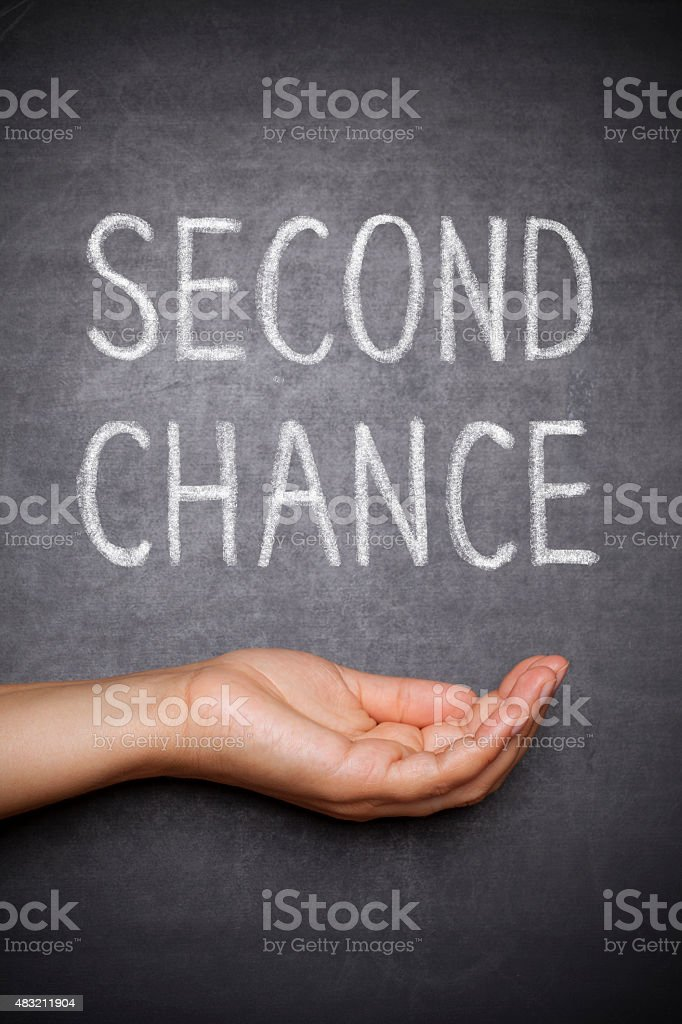 hand holding ,, second chance\' written on blackboard
