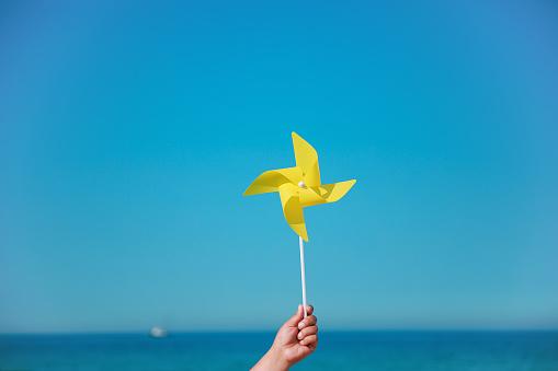 Hand holding yellow pinwheel in the sea