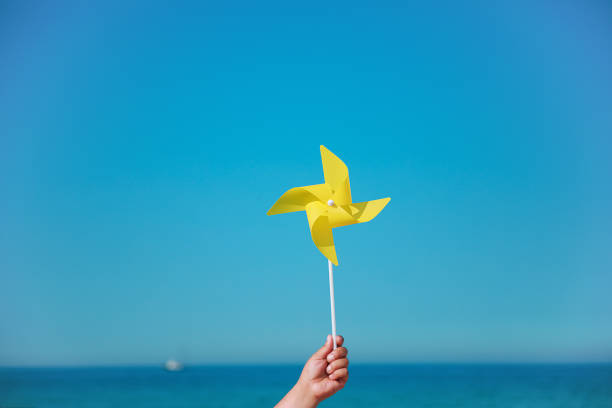 Hand holding yellow pinwheel in the sea stock photo