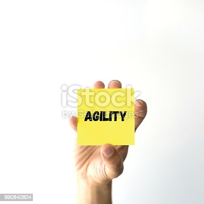 1144568493 istock photo Hand holding yellow sticky note written AGILITY word 990840804