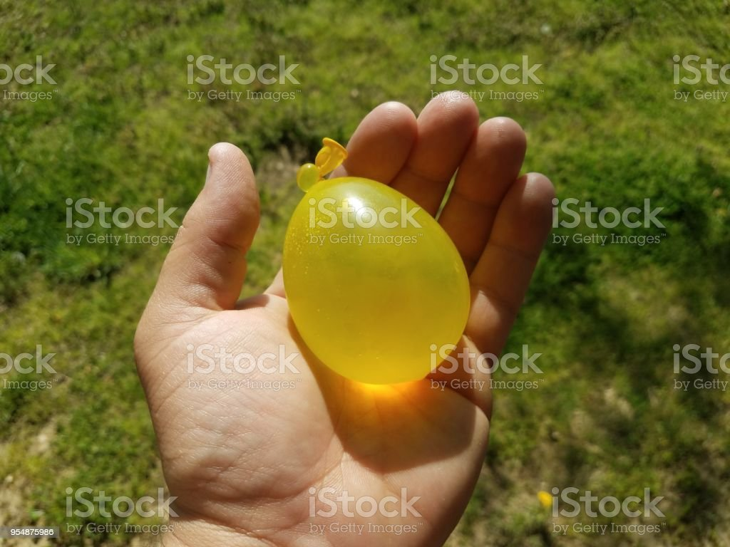 hand holding yellow water balloon over green grass stock photo
