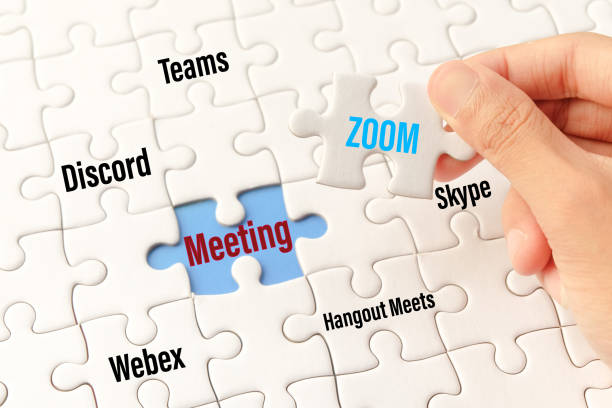 bangkok, thailand - may 10, 2020 : hand holding zoom word on white jigsaw puzzle is connect to meeting word on blue gap - idea match (teams, discord, webex, hangout meets, skype) concept.bangkok, thailand - may 10, 2020 : hand holding zoom word on white j - skype imagens e fotografias de stock