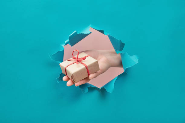 Hand holds a craft gift through a torn paper hole. Special offer, sale, bonus, present stock photo