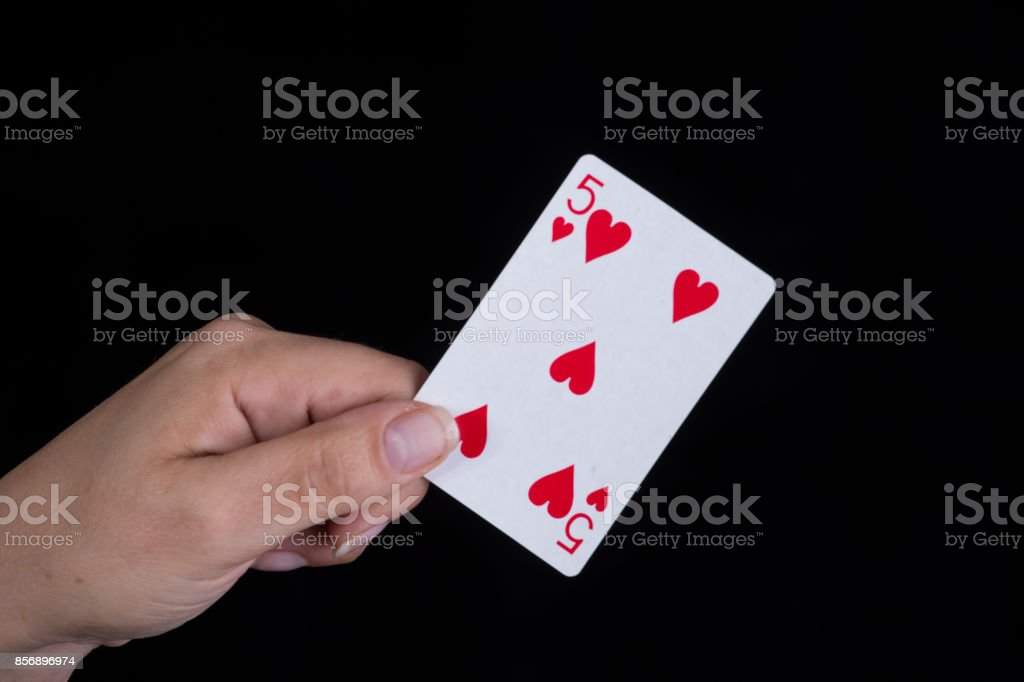 Hand holds a five of hearts card stock photo