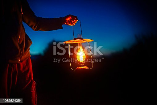 istock hand holds a large old lamp in the dark. 1065624054