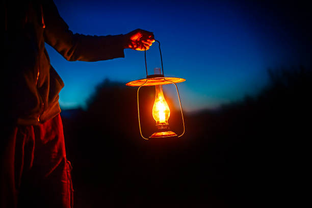 hand holds a large old lamp in the dark. man holding the vintage lamp with a candle outside. Copy space for your text lantern stock pictures, royalty-free photos & images