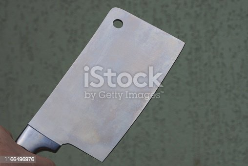 hand holds a large steel cleaver on a gray background