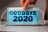 istock hand holds a medical and protective mask with the word GOODBYE 2020. Concept of coronavirus quarantine. Prevent or stop the spread of the COVID-19 worldwide. 1282637509