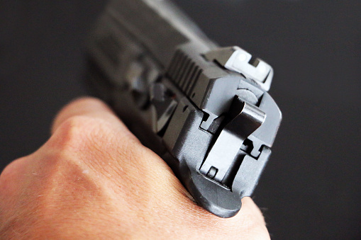 istock A hand holds a pistol aimed at the target 1152175710