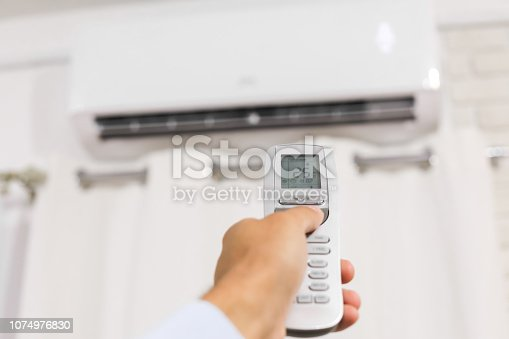 istock hand holds a remote control of air conditioner 1074976830