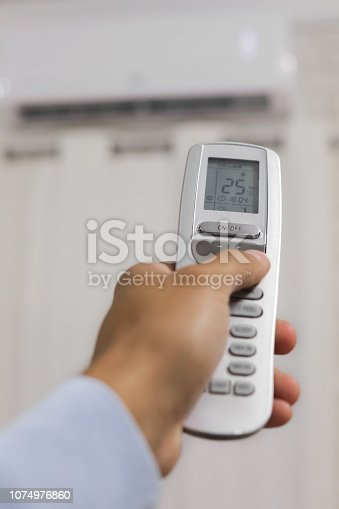 istock hand holds a remote control of air conditioner 1074976860