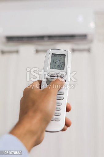 istock hand holds a remote control of air conditioner 1074976862