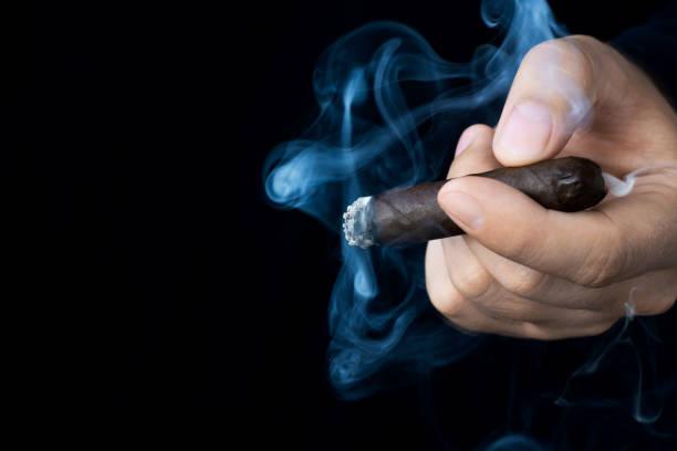 een hand houdt een smeulende sigaar in rook tegen een donkere achtergrond. ruimte links voor tekst. - guy with cigar stockfoto's en -beelden