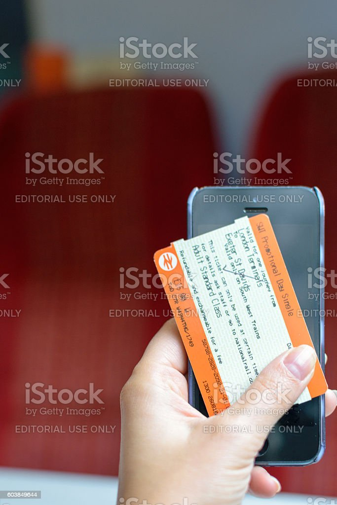 Hand holds a train ticket and a smartphone stock photo
