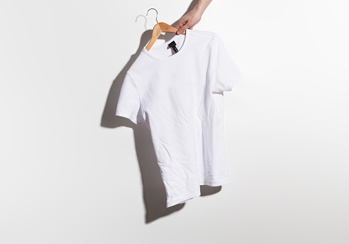 Hand holds a white crumple t-shirt on wooden hangers, on a gray background