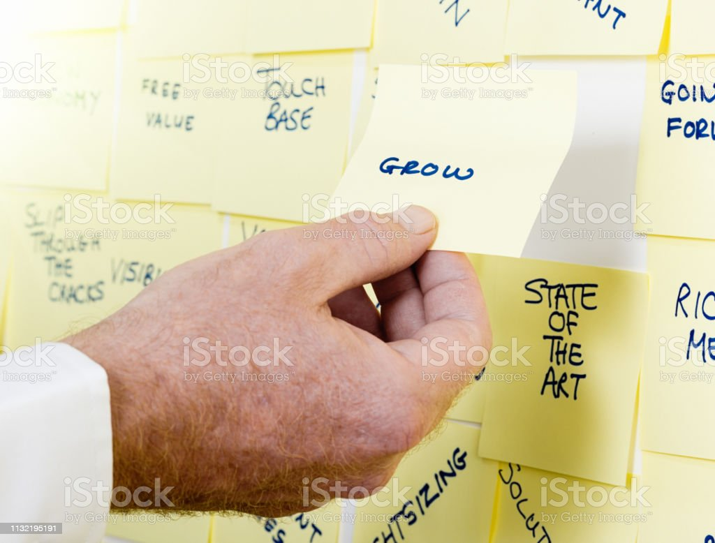 A male hand holds a yellow adhesive note reading \'grow\' next to a...