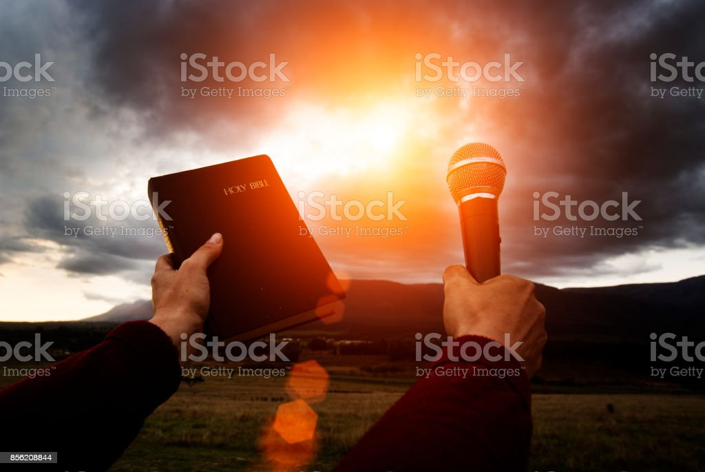 Hand holds bible and microphone up towards gray clounds stock photo