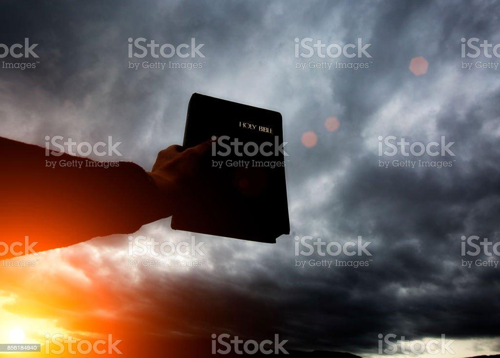 Hand holds bible up towards grey clounds stock photo