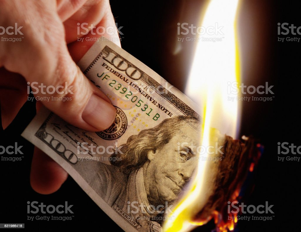 Hand holds burning American Hundred Dollar bill stock photo