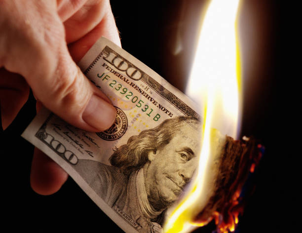 Hand holds burning American Hundred Dollar bill PLEASE NOTE: The $100 bill was not harmed. The flame is comped in. money to burn stock pictures, royalty-free photos & images