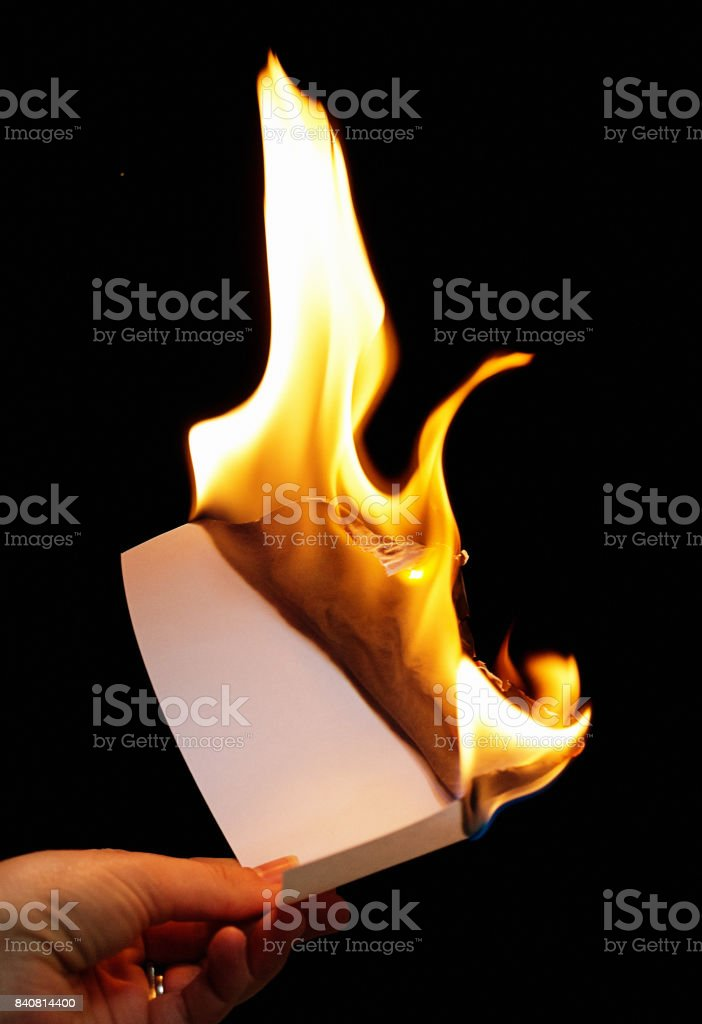 Hand holds burning piece of paper stock photo