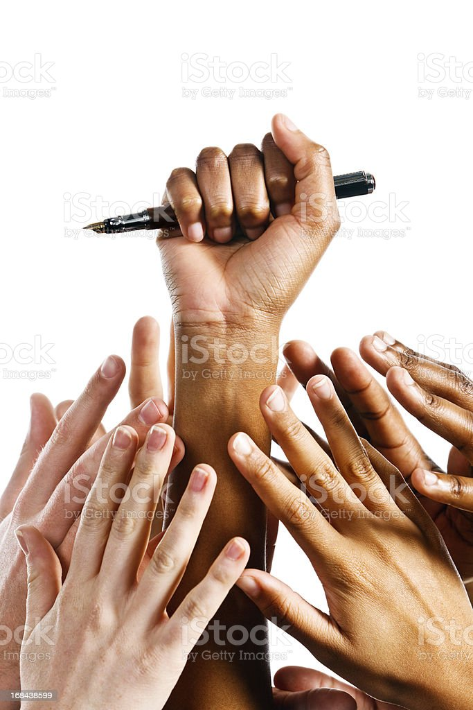 Hand holds fountain pen as many reach up for it stock photo