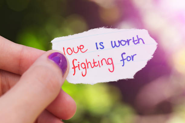 """Hand holds hand-drawn """"love is worth fighting for"""" note A female hand holds a little hand-drawn love note reading """"love is worth fighting for"""". cute teen couple stock pictures, royalty-free photos & images"""