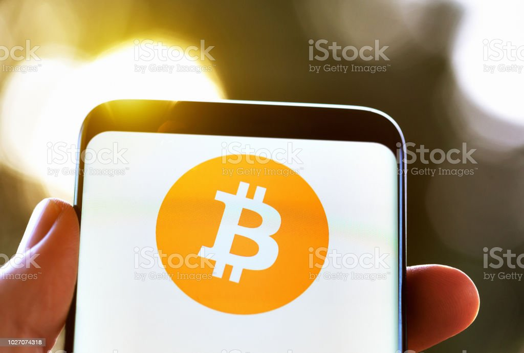 Hand holds mobile phone showing Bitcoin logo stock photo