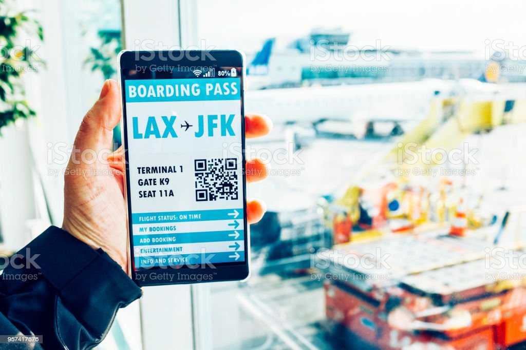 Hand holds mobile phone which shows electronic boarding pass and QR code stock photo